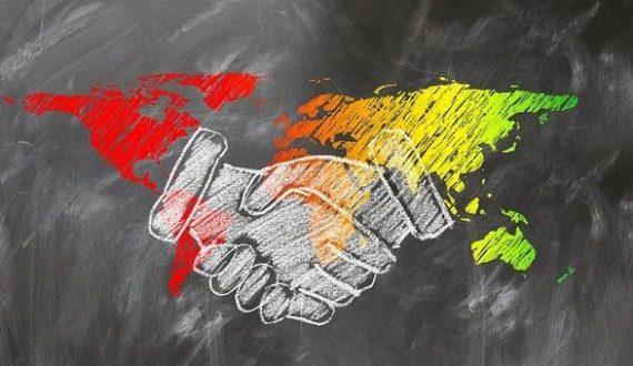 Image d'une poignée de main avec les 5 continents en arrière-plan